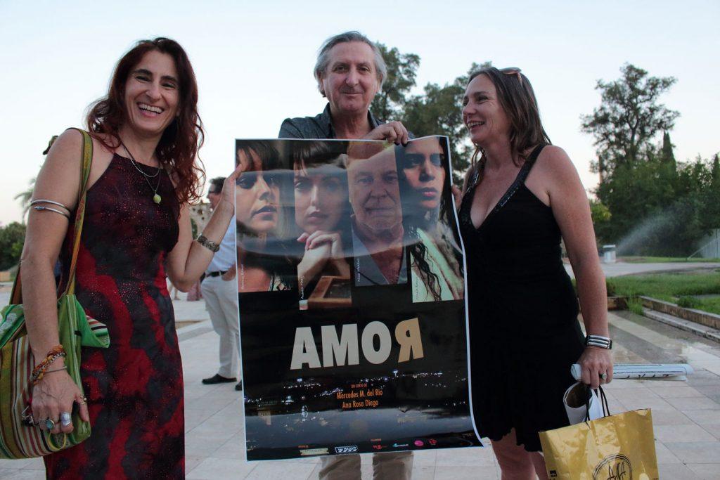 Ana Rosa Diego, Mercedes del Río y Sebastián Haro junto al cartel del cortometraje Amor